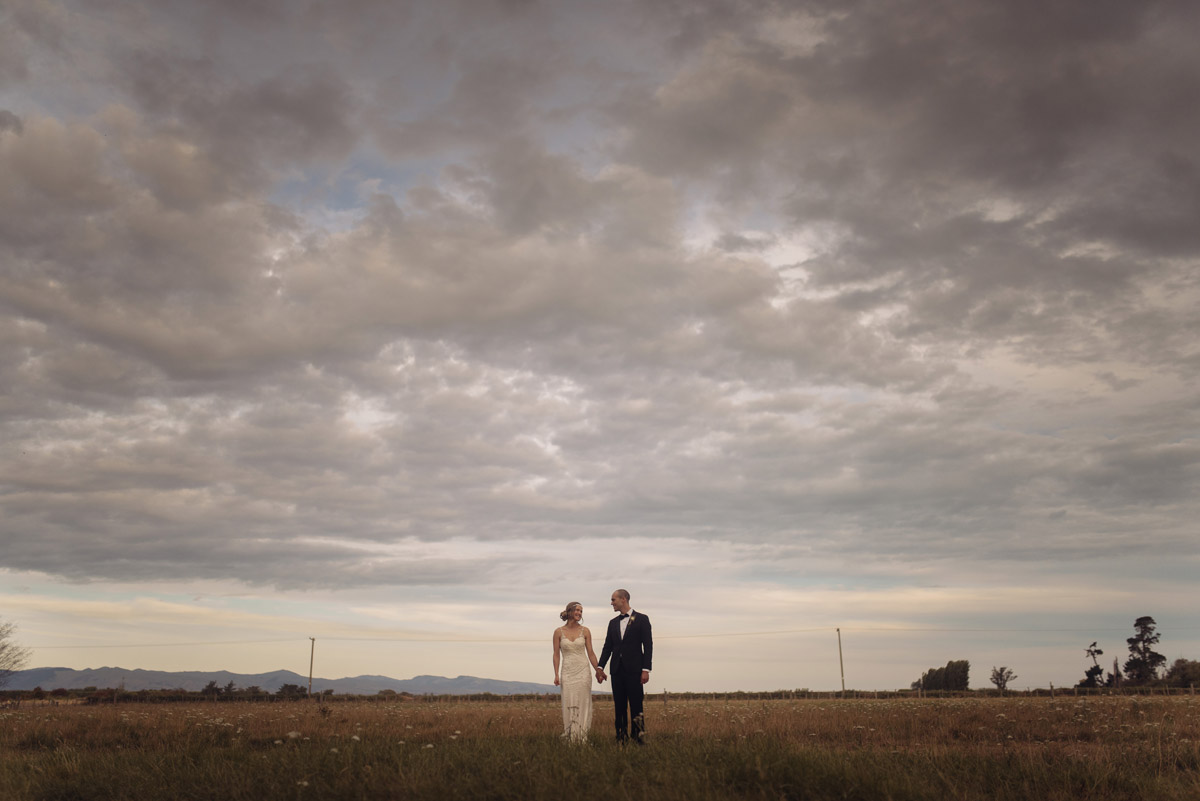 Couple standing in a field, on their wedding day. Photograph by Emma Brittenden.